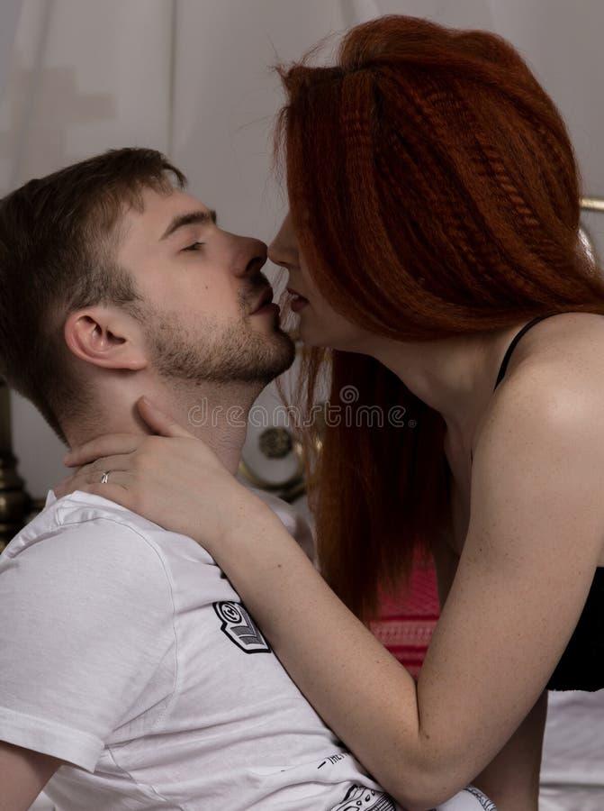 El par cariñoso hermoso joven está abrazando en una cama imagen del ntimate del foreplay sensual de los pares, besándose apasiona fotos de archivo