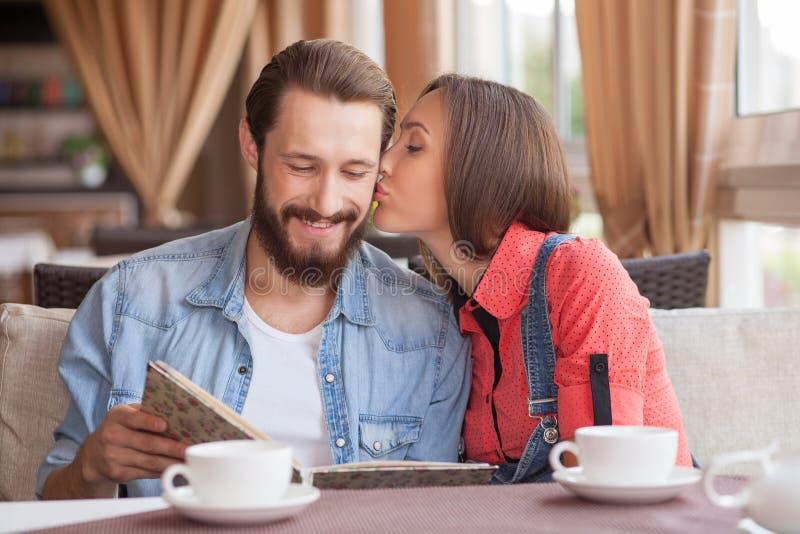 El par cariñoso joven alegre está fechando en café fotografía de archivo libre de regalías