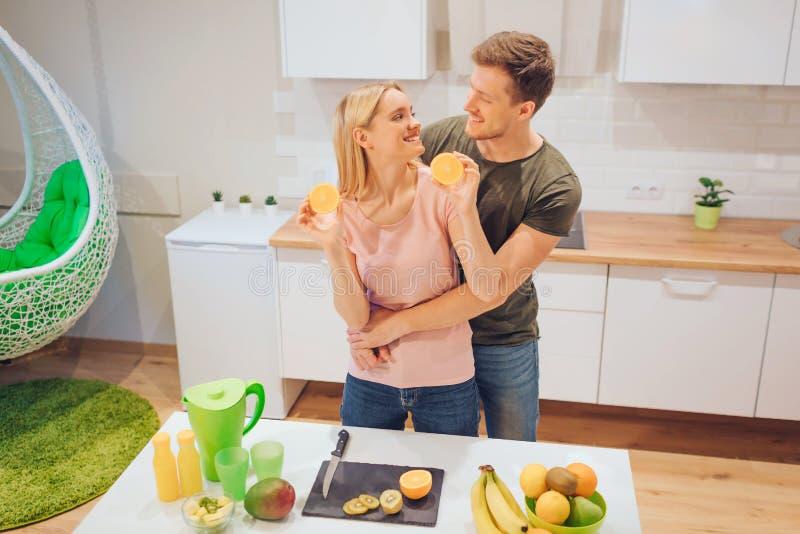 El par cariñoso joven se divierte con la naranja orgánica mientras que cocina las frutas frescas en la cocina blanca Alimento san foto de archivo libre de regalías