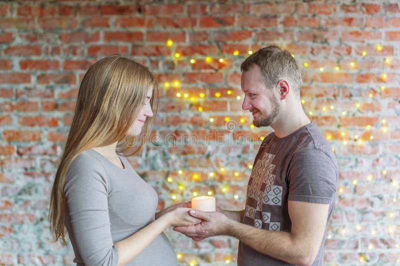 El par cariñoso lleva a cabo la vela ardiente disponible La mujer está embarazada imagen de archivo libre de regalías