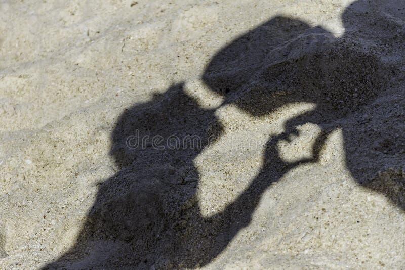El par cariñoso sombrea la fabricación de un beso en la playa tropical de la arena imagenes de archivo