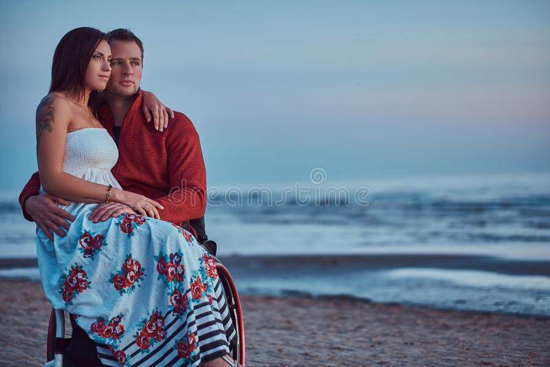 El par cariñoso, una mujer se sienta en su revestimiento del ` s del marido, basándose sobre una playa contra un fondo de un aman foto de archivo