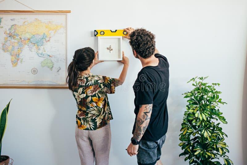 El par cuelga la pintura del marco en la pared imagen de archivo