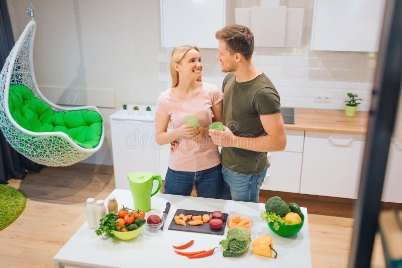 El par de amor del vegano lleva a cabo bebidas del detox mientras que cocina verduras crudas en la cocina Detox de la dieta dieta fotos de archivo libres de regalías