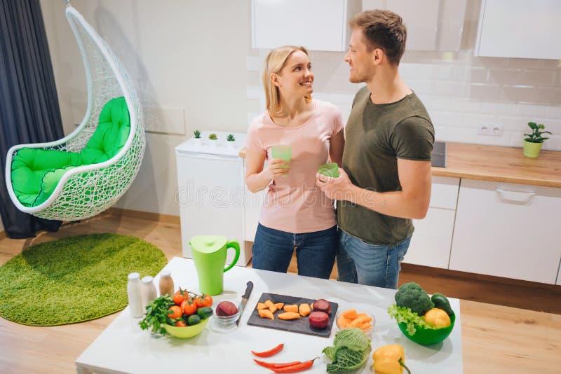 El par de amor feliz del vegano lleva a cabo bebidas del detox mientras que cocina verduras crudas en la cocina Detox de la dieta foto de archivo