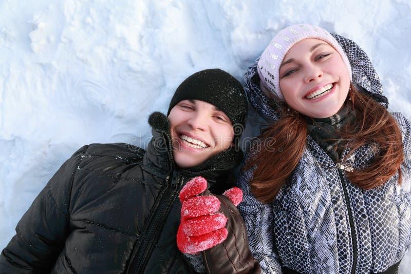 El par de gente de los amantes miente en nieve y risa fotos de archivo libres de regalías