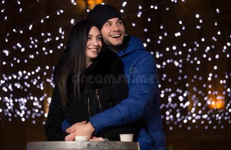 El par de la mujer del hombre joven, noche, invierno viste la sonrisa feliz imagen de archivo