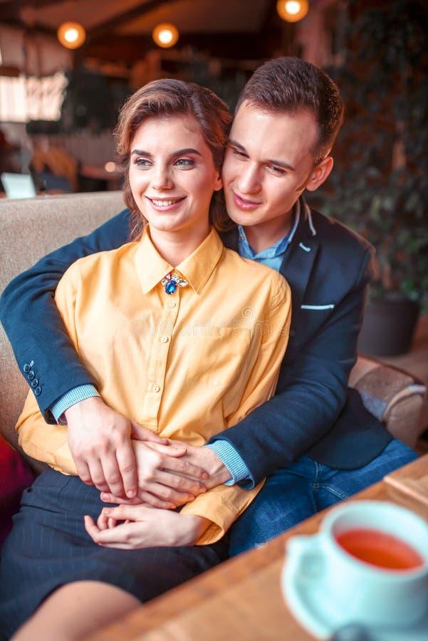 El par del amor abraza y mirando la ventana foto de archivo