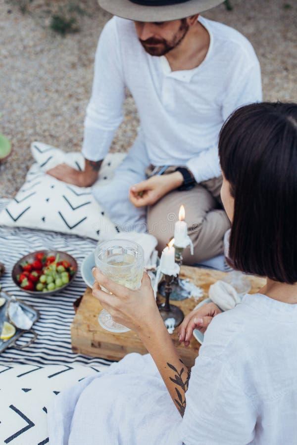 El par del inconformista bebe el vino en comida campestre imagenes de archivo