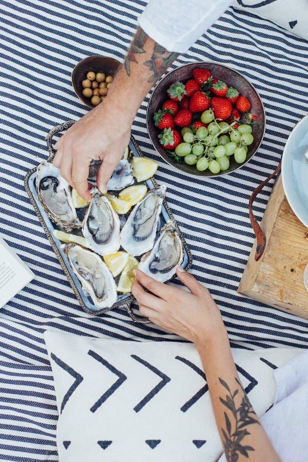El par del inconformista goza de ostras frescas fotos de archivo