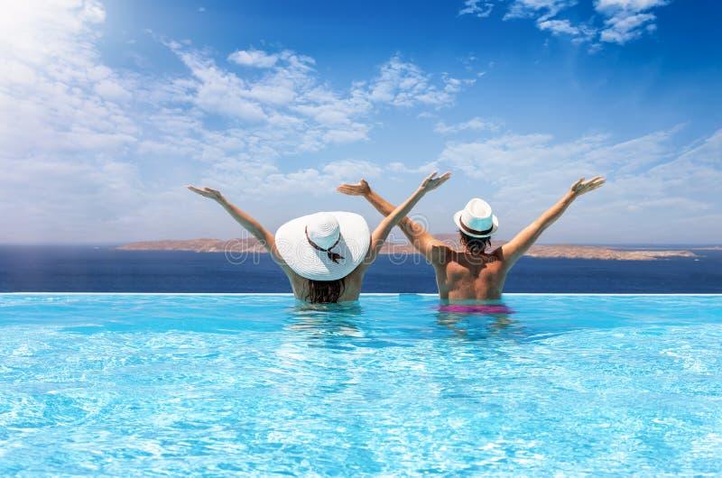 El par del viajero disfruta de la visión al mar Mediterráneo en una piscina imagenes de archivo