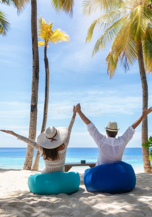El par disfruta de sus vacaciones tropicales en una barra de la playa fotos de archivo