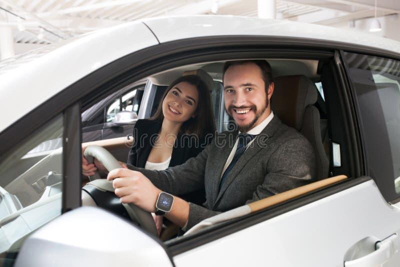 El par elige el coche en la sala de exposición fotos de archivo