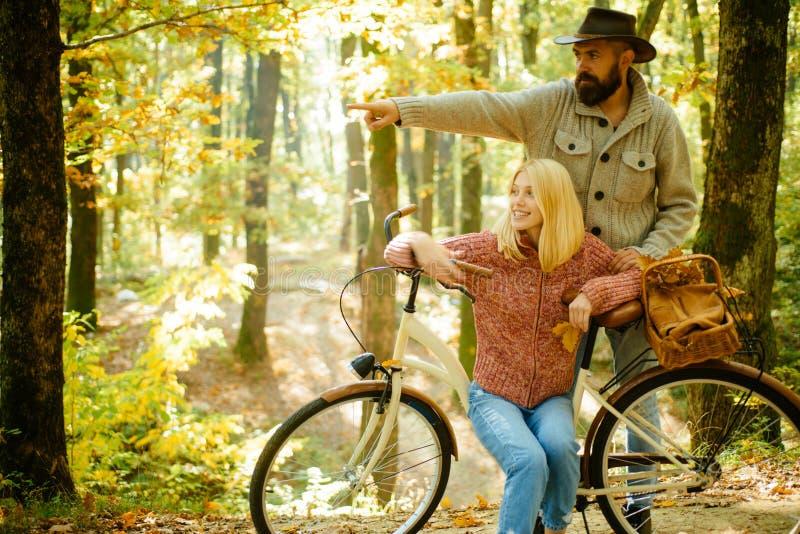El par en amor está montando la bicicleta en el parque Gente activa outdoors Pares del otoño que llevan en ropa del otoño fotografía de archivo