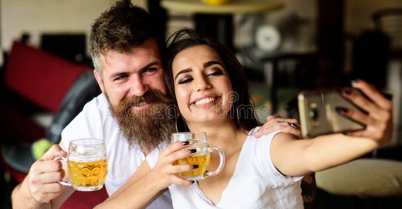 El par en amor el fecha bebe la cerveza Mejores amigos o amantes que beben la cerveza en pub Inconformista y muchacha barbudos de imagen de archivo libre de regalías