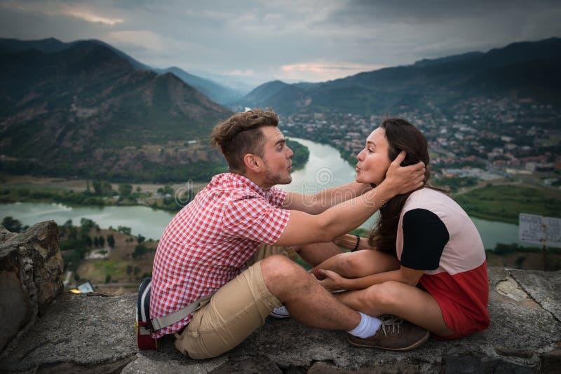 El par en amor se sienta en la piedra en el fondo de montañas fotografía de archivo libre de regalías