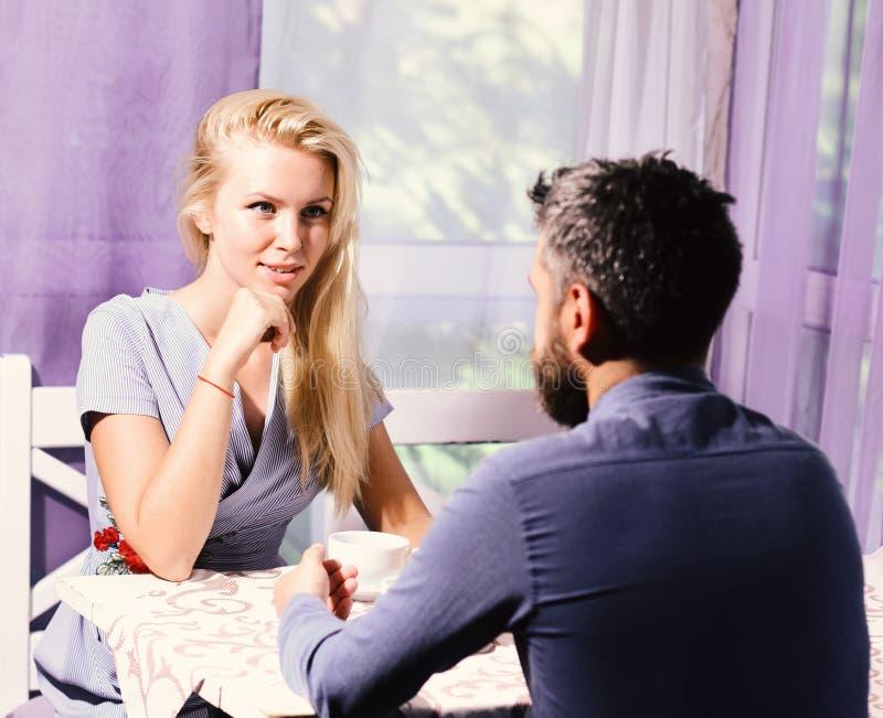 El par en amor sostiene las tazas de café en la tabla La mujer y la cara coqueta y el hombre tienen un asunto imagen de archivo