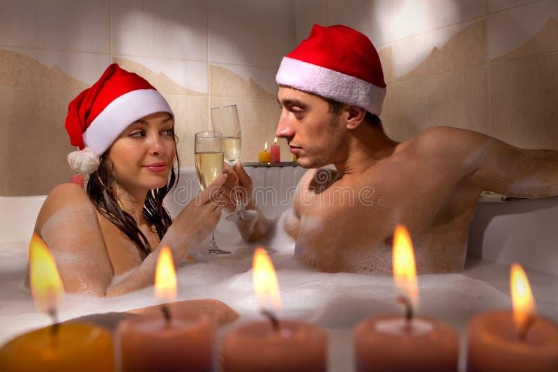 El par en los sombreros de santa está disfrutando de un baño fotos de archivo