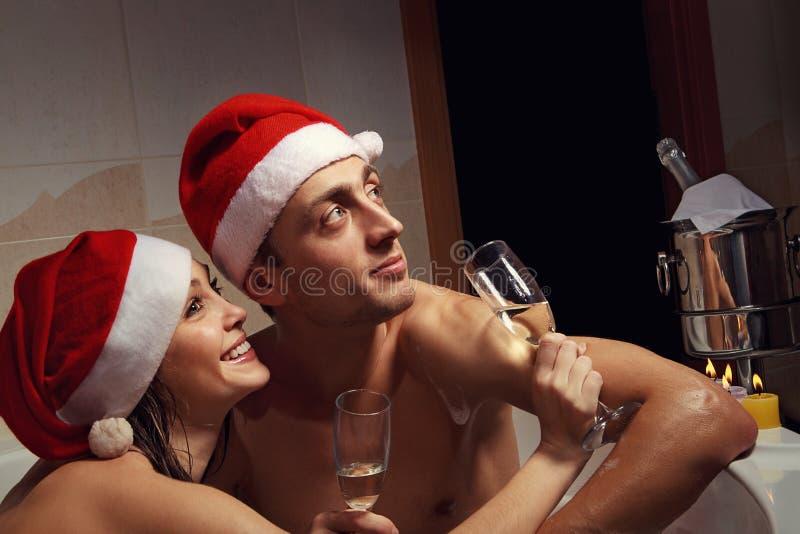 El par en los sombreros de santa está disfrutando de un baño fotografía de archivo
