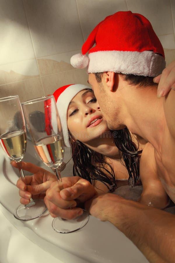 El par en los sombreros de santa está disfrutando de un baño fotografía de archivo libre de regalías