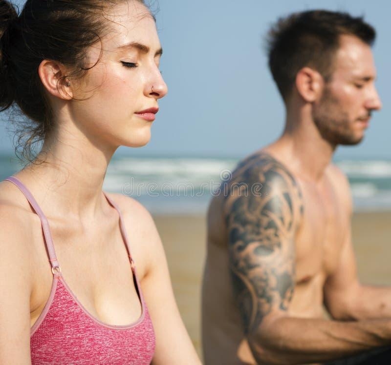 El par está haciendo una yoga en la playa fotos de archivo