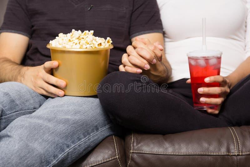 El par está mirando película en casa Completamente cerrado, anónimo hombre y fotografía de archivo