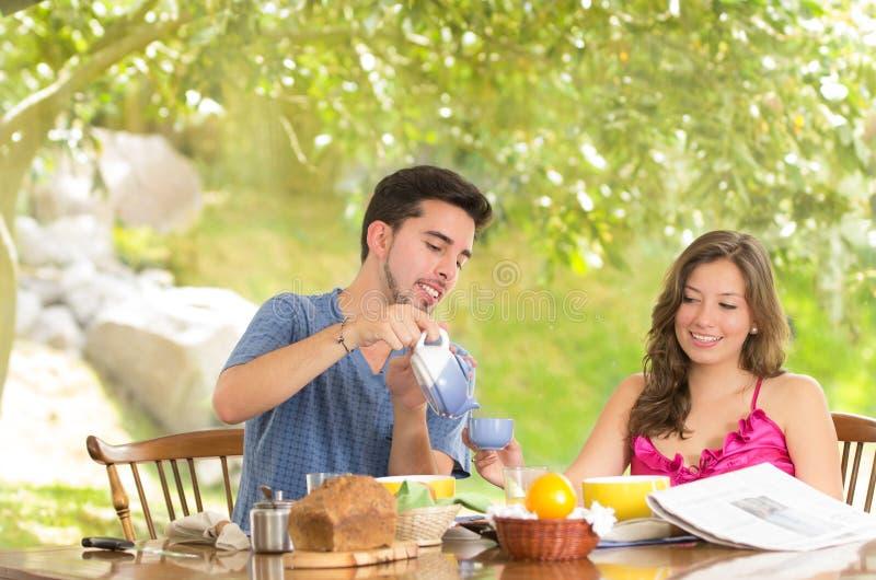 El par feliz, atractivo come el desayuno junto fotografía de archivo libre de regalías