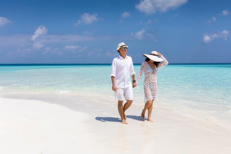 El par feliz camina abajo de una playa tropical fotografía de archivo