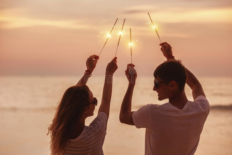 El par feliz celebra puesta del sol con las bengalas fotografía de archivo libre de regalías