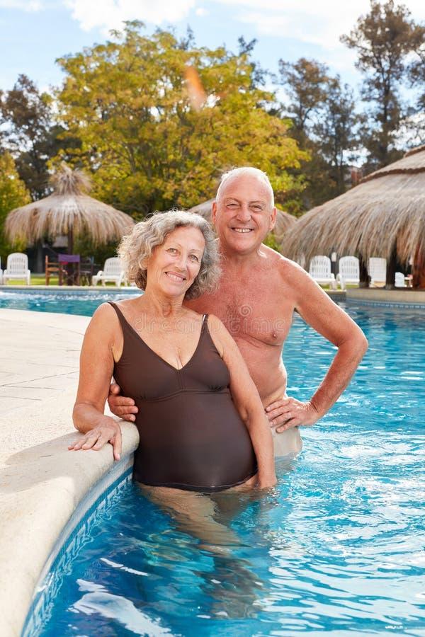 El par feliz de mayores se está colocando en piscina en vacaciones de verano foto de archivo