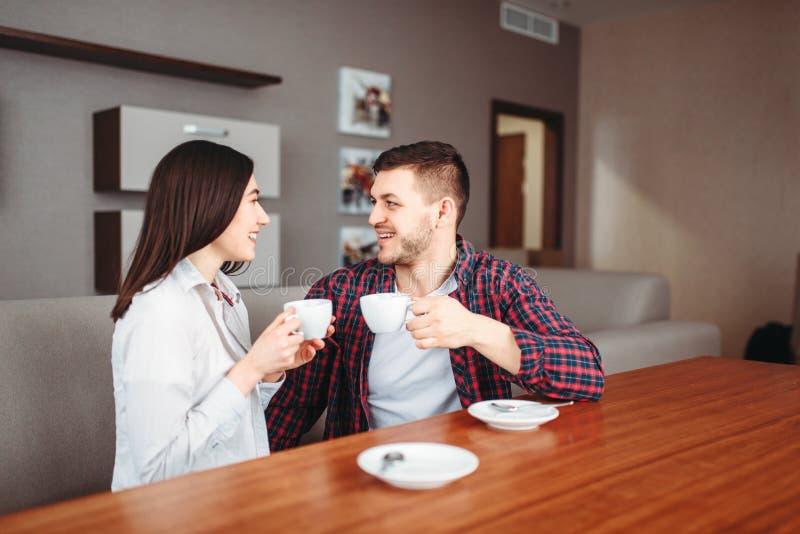 El par feliz del amor bebe el café en la tabla de madera imagenes de archivo