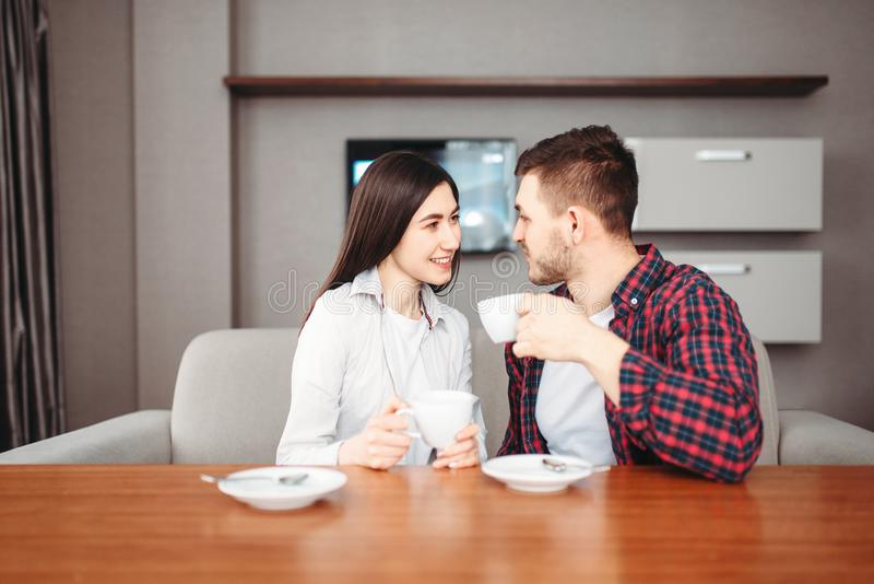El par feliz del amor bebe el café en la tabla de madera fotografía de archivo libre de regalías