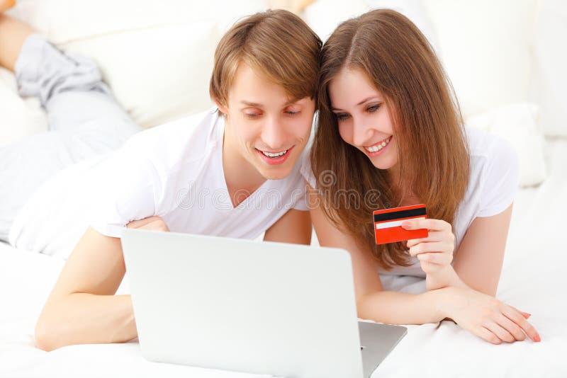 El par feliz hace compras en línea con el ordenador portátil y la tarjeta de crédito a fotos de archivo libres de regalías