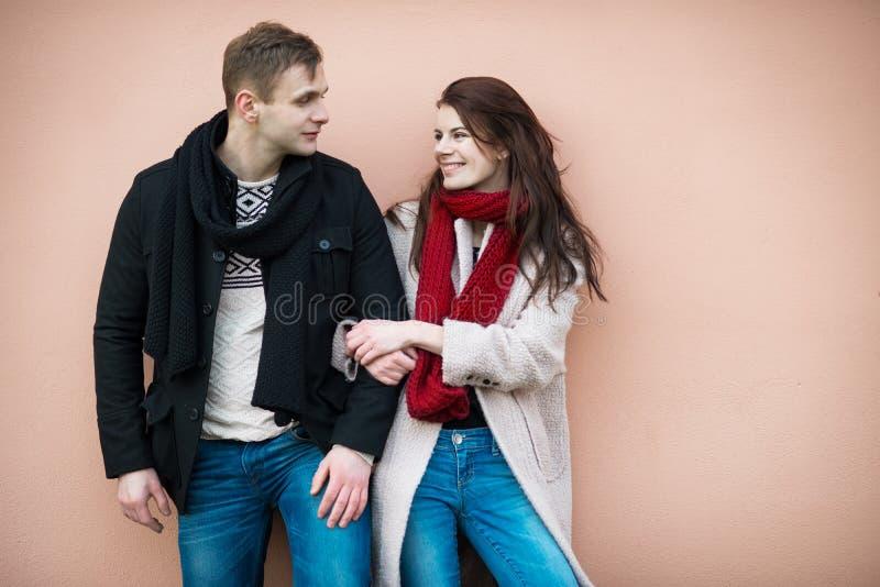 El par feliz hermoso en invierno viste cerca de la pared fotos de archivo libres de regalías