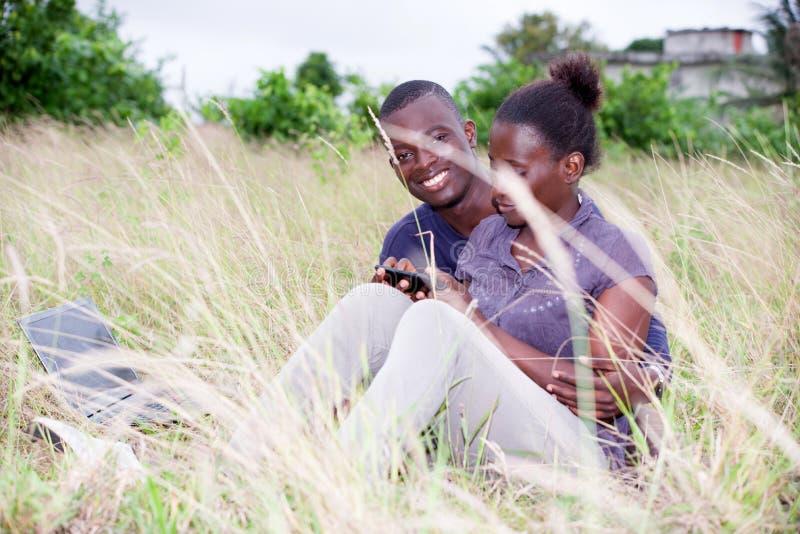El par feliz se relaja en la hierba en verano fotos de archivo