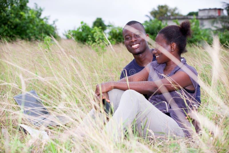 El par feliz se relaja en la hierba en verano imagenes de archivo
