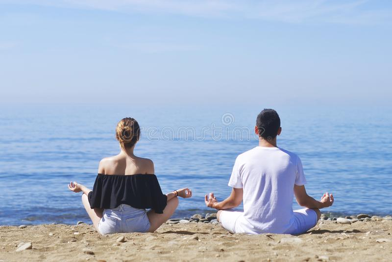 El par hace la meditación en actitud del loto en el mar/la playa, la armonía y la reflexión del océano Yoga practicante del mucha fotos de archivo libres de regalías