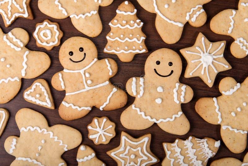 El par hecho en casa del pan de jengibre de la Navidad, abetos, protagoniza las galletas sobre fondo de madera imágenes de archivo libres de regalías