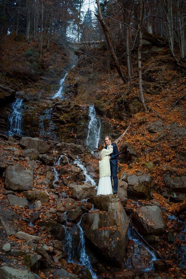 El par hermoso de la boda abraza en la cascada, fondo del bosque del otoño imagen de archivo