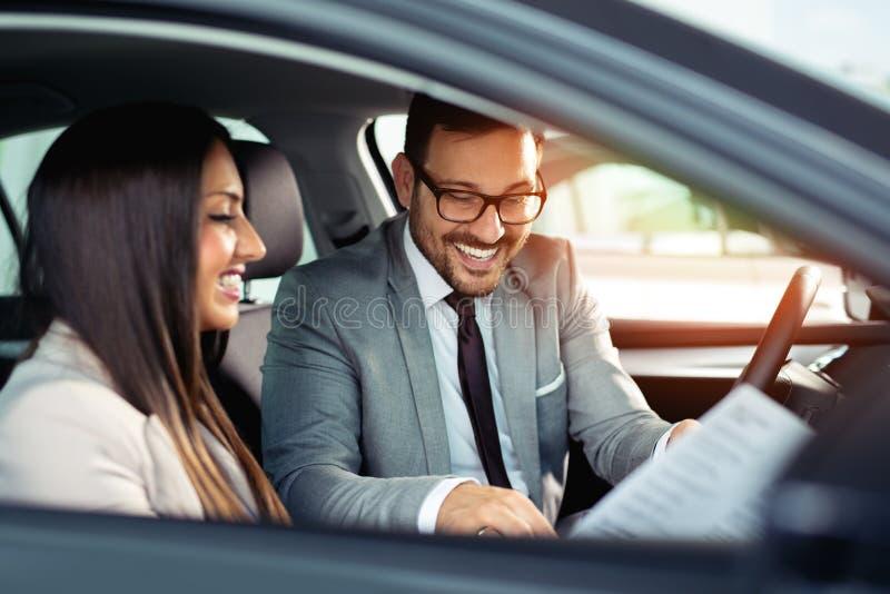 El par hermoso es que habla y sonriente mientras que se sienta en su nuevo coche imagenes de archivo