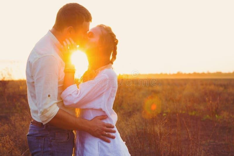 El par hermoso joven que se besa contra puesta del sol irradia al aire libre en campo en puesta del sol foto de archivo libre de regalías