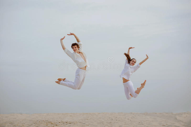 El par hermoso y positivo realiza salto simultáneo encima del alto fotos de archivo
