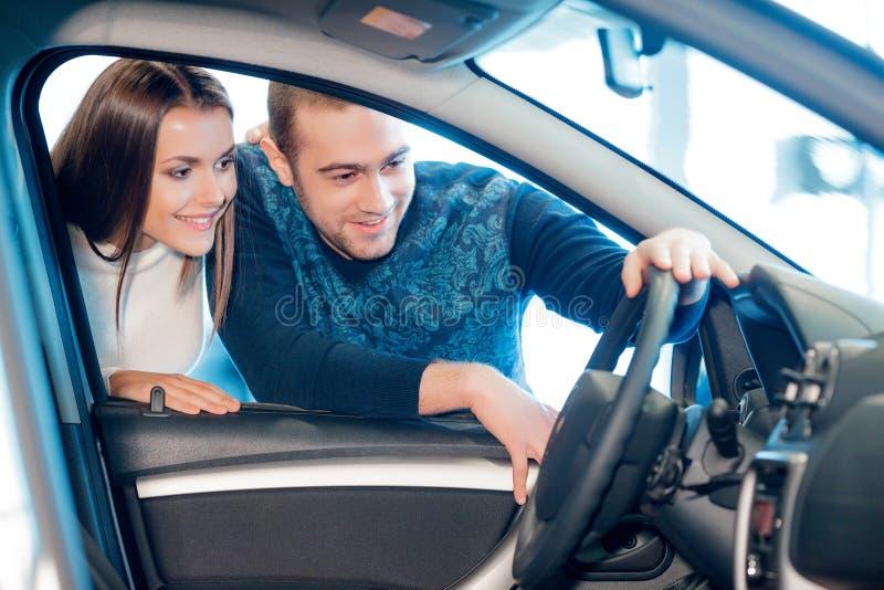 El par interesado examina un nuevo coche en la sala de exposición imagen de archivo