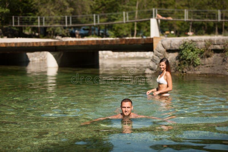 El par joven activo juega en agua poco profunda en un morni caliente del verano imagen de archivo