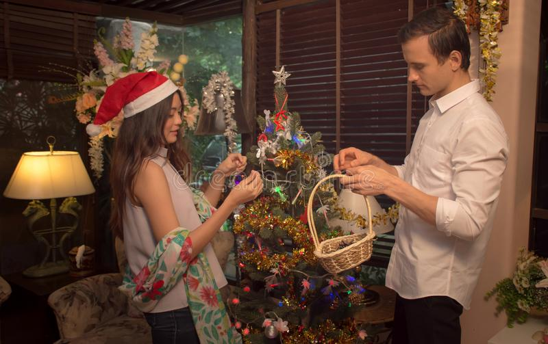 El par joven adorna el árbol de navidad en una casa/un concepto imerry de la Navidad imagenes de archivo