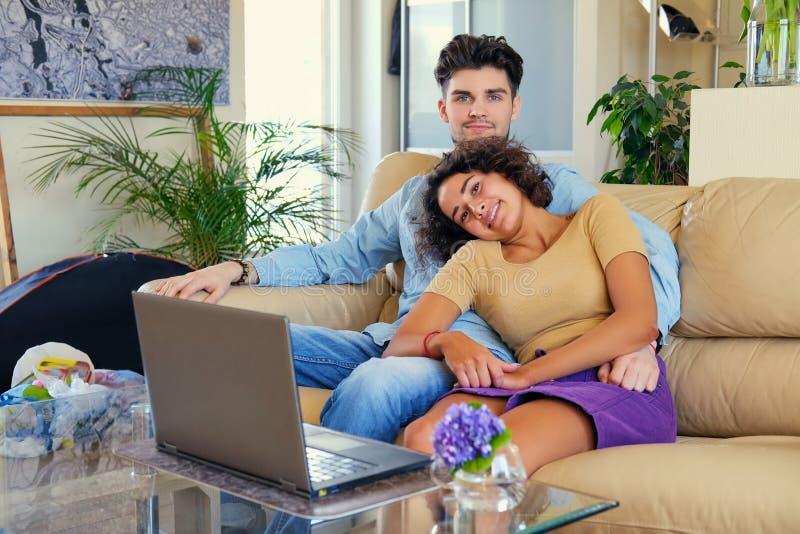 El par joven atractivo se sienta en un sofá con un ordenador portátil en una tabla en una sala de estar imagen de archivo libre de regalías