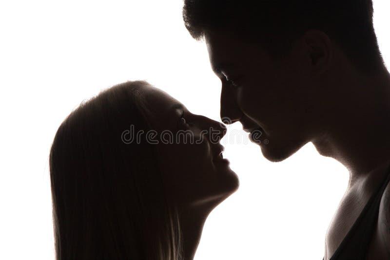 El par joven atractivo sensual apasionado en amor, hombre acaricia el cuello de la mujer, retrato blanco y negro aislado imagen de archivo