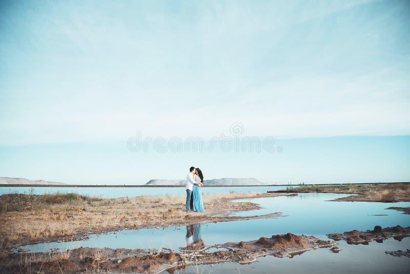 El par joven en amor está descansando junto cerca del lago y las montañas, la mujer caucásica hermosa y el hombre cayeron en amor imagenes de archivo
