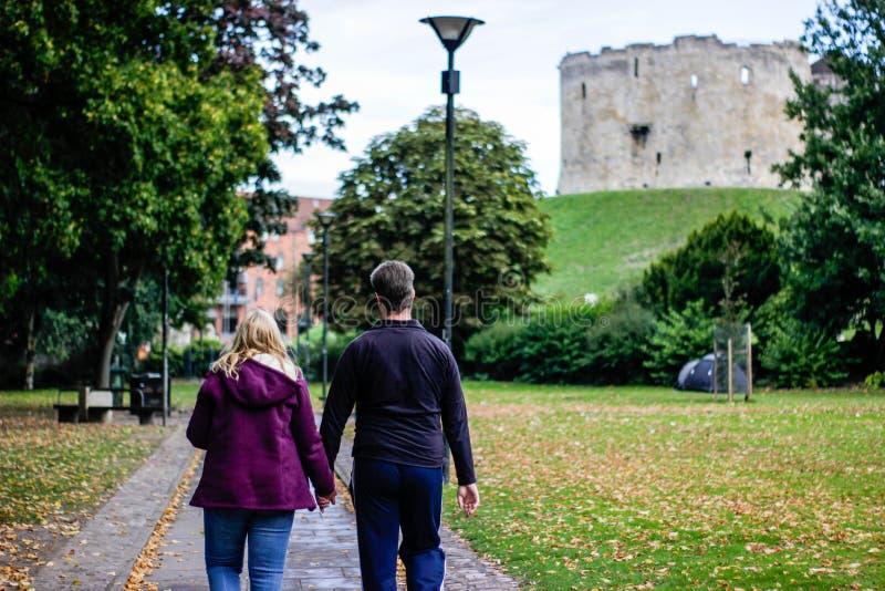 El par joven está caminando alrededor de la torre de Clifford en York en septiembre de 2018 foto de archivo libre de regalías