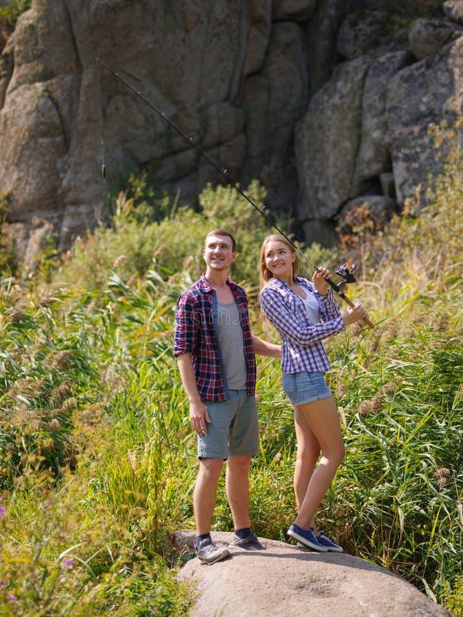 El par joven está disfrutando de pesca el día soleado imagen de archivo